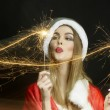 Beautiful woman in Santa Claus outfit with New year party sparklers on black background — Stock Photo #60159989