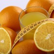 Orange fruits, juice and measuring tape — Stock Photo #68217547