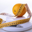 Orange and measuring tape on scales — Stock Photo #68218191