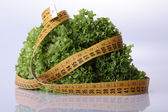 Salad lettuce and measuring tape — Stock Photo