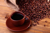Cup and heap of coffee beans — Stock Photo