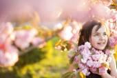 Little girl amid cherry flowering — Stock Photo