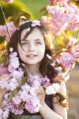 Little girl amid cherry blooming — Stock fotografie