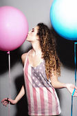 Happy young beautiful girl kissing balloons — Stock Photo