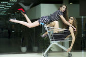 Two attractive girls in shopping trolley — 图库照片