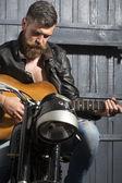 Biker man with guitar — Stock Photo