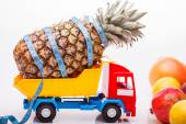 Pineapple with tape-measure and fruits on lorry — Stock Photo