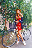 Portrait of young woman riding her vintage bicycle — Stock fotografie
