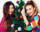 Women posing near Christmas tree — Stock Photo