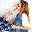 Hipster girl having fun, eating banana from another hand. — Stock Photo #62171121