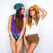 Hipster girls posing at wall background — Stock Photo