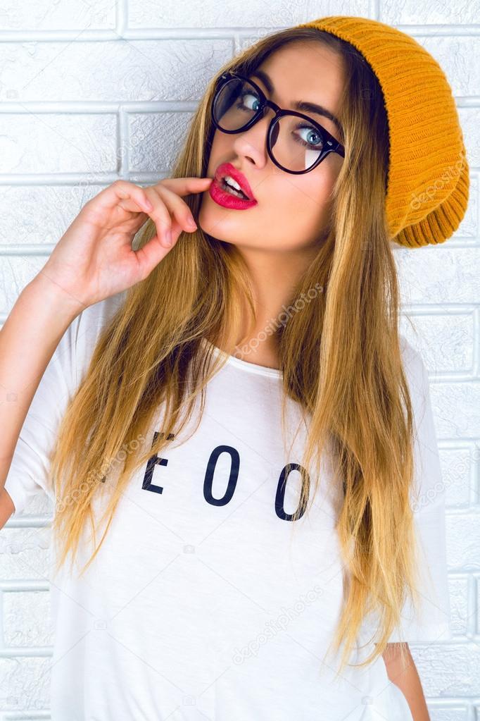 Retrato de estudio de moda de hipster bastante joven mujer rubia con brillantes sexy maquillaje y gafas, vistiendo camiseta urbana elegante y sombrero,