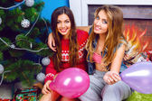 Sisters sitting at home near Christmas tree — Stock Photo