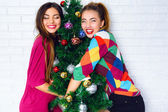 Girls posing near Christmas tree — Stock Photo