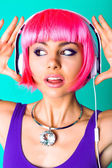 Woman in pink wig and earphones — Stock Photo
