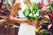 Slim woman holding wedding bouquet — Stock Photo
