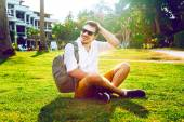 Young hipster man sitting on the grass — Stock Photo
