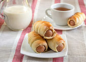 Hot-dog with sausages in a plate with tea and milk — Stock Photo