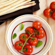 Cherry tomatoes with asparagus and basil leaves — Stock Photo #60367351