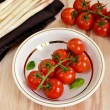 Cherry tomatoes in a white plate with asparagus and basil leaves — Stock Photo #60369799