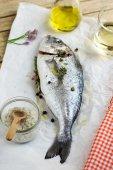 Fresh fish gilt-head bream dorade with salt and pepper — Stock Photo
