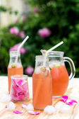 Rhubarb hibiscus iced tea with rose petals in the garden — Stock Photo