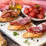 Italian bruschettas with ham prosciutto, coppa and salami — Stock Photo #75844191