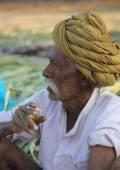 Indian man with green turban smoking a cigarette — Stock Photo