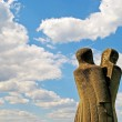 Постер, плакат: A stone sculpture of two people or split personality on the ba