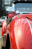 Interesting shape of old red car with original mirror close up.  — Stock Photo