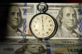 The timer on the background of dollar bills (advantages and disa — Stock Photo