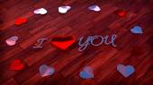 Glossy heart shapes on wood floor with sign I love you — Stock Photo
