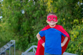 Superhero standing with hands on hips and smiling — Stock Photo