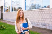 Student standing on building background and smiling — Stock Photo