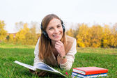 Student listening to headphones and reading book — Stock Photo