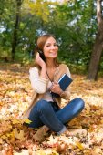 Student sitting with headphones among maple leaves — Stock Photo