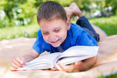 Boy lying on picnic and reading book — Stock Photo