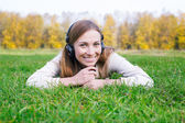 Student propping head and listening to headphones — Stock Photo