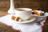 Cup of tea with sugar cubes and cake — Photo