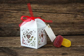 Gift box with chocolates on a wooden background — Photo