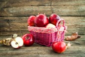 Red apples in a basket on wooden background — Stock Photo