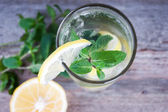 Lemonade with fresh lemon and mint in glass on wooden background — Stock Photo