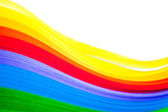 Rainbow colored quilling paper laid out in waves and shapes — Stock Photo
