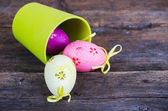 Easter eggs in the basket on rustic wooden background — Stock Photo