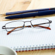 Glasses on notebook with pen and cup of coffee in wood table — Stock Photo #71922265