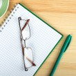 Glasses on notebook with pen and cup of coffee in wood table — Stock Photo #71922521