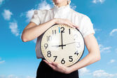 Business woman holding a clock on the sky backround — Stock Photo