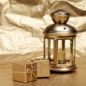Candle and gifts on a gold background — Stock Photo