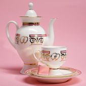 Tea set with candy on pink background — Stock Photo