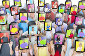 People holding tablets in front of faces — Stock Photo